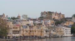 People on Gangaur Ghat with city palace,Udaipur,India Stock Footage