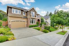 Beautiful curb appeal of American house with stone trim and perfectly trimmed Stock Photos