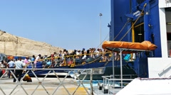 Tourists boarding a ferry at Santorini's port heading to the island of iOS Stock Footage