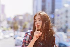 Mysterious girl asking to keep her secret Stock Photos