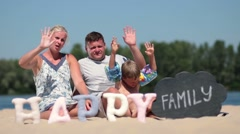 Happy family sitting on the beach and waving hello Stock Footage