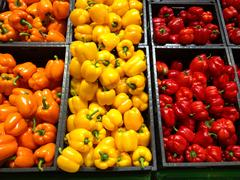 Set of peppers orange yellow and red lying in boxes in supermarket Stock Photos