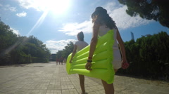 Two girls with inflatable water bed walking toward beach Stock Footage