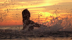 SLOW MOTION: Smiling young girl playing with water in ocean at golden sunset Stock Footage