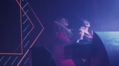 Dj girl and mc girl energy dance at turntable in club. Raise hands. Illumination Stock Footage
