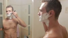 Man shaves his face. handsome man shaving in the bathroom. Stock Footage