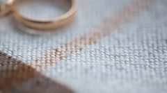 Two bridal rings lie on knitted surface of tablecloth Stock Footage