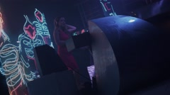 Dj girl in headphones red dress perform at turntable in nightclub. Dancing Stock Footage