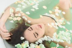 Attractive girl pampering in water with flowers Stock Photos