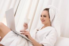 Pretty girl entertaining with computer at spa - stock photo