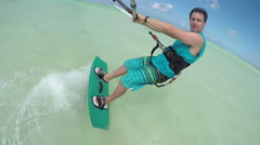 CLOSE UP: Happy young kiter kiteboarding in perfect blue lagoon on Zanzibar Stock Footage