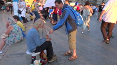 WYD Krakow 2016 - man giving a saint picture to a old beggar in street Stock Footage