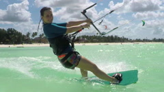 SLOW MOTION: Happy young surfer woman kiteboarding in beautiful blue lagoon Stock Footage