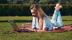 Young woman relaxing with her laptop on the grass Stock Footage