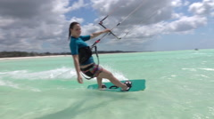 SLOW MOTION: Smiling surfer girl kitesurfing past the camera in blue lagoon Stock Footage