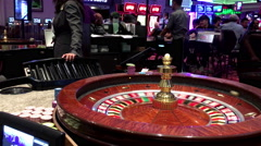 Motion of people playing casino roulette and  ball stops at red nine - stock footage
