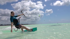 SLOW MOTION: Cheerful surfer girl has fun kitesurfing in amazing emerald ocean Stock Footage