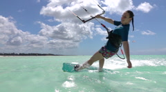 SLOW MOTION: Happy young surfer girl kiteboarding in perfect blue ocean Stock Footage