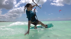 SLOW MOTION: Happy surfer girl kiteboarding and doing hand drag splashing water Stock Footage