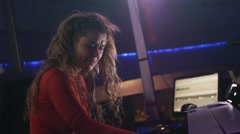 Dj girl in red dress spinning at turntable on party in nightclub. Mc man Stock Footage