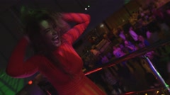 Dj girl in red dress dance at stand on party in nightclub. Spotlight. Shake head Stock Footage