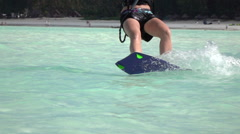SLOW MOTION CLOSEUP: Young kitesurfer woman kiteboarding in perfect blue lagoon Stock Footage