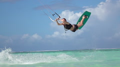 SLOW MOTION CLOSEUP: Young surfer girl kiteboard jumping the rally in blue ocean Stock Footage