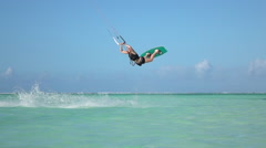 SLOW MOTION CLOSEUP: Extreme kite girl kiteboard jumping rally in blue lagoon Stock Footage