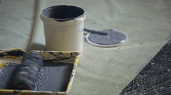 Worker dips paint roller into ditch with gray paint on floor near jar Stock Footage