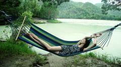 Woman relaxes in hammock, swaying gently, in wood Stock Footage