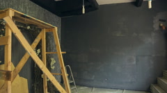 Young builder accurately paints wall with gray suffusion in art studio Stock Footage