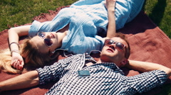 Attractive young couple relaxing in the summer sun Stock Footage