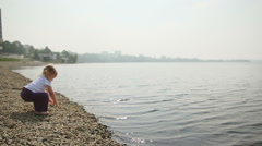 Girl throwing stones into the pond. Stock Footage