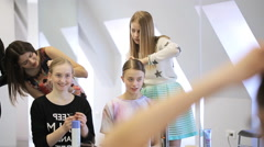 Stylists create hairstyle for pretty girls in white studio Stock Footage