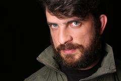 Bearded guy in khaki jacket with interesting look. Close.up. Black Stock Photos