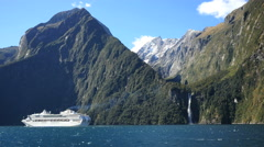 New Zealand Milford Sound cruise ship and waterfall Stock Footage