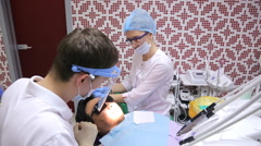 Young dentist asks about health of patient is in chair, nurse assists - stock footage