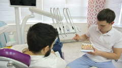 A man with a beard lying in dental chair, next to telling and showing on model Stock Footage