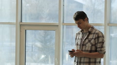 A young man in a plaid shirt stands in front of panoramic windows and keep Stock Footage