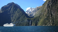 New Zealand Milford Sound waterfall and cruise ship Stock Footage