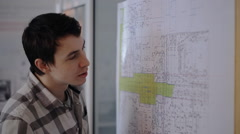 A young student engineer working on communications plan of city with pencil in Stock Footage