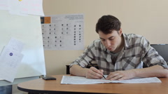 Young man bent over plan on table and draws on it with a pen sitting Stock Footage