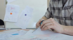 A man in a plaid shirt, a pair of scissors cuts tracing paper which shows plan Stock Footage
