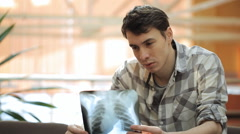 Young man attentively looks at roentgenogram of lungs Stock Footage