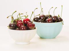 Two bowls of wet cherries Stock Photos