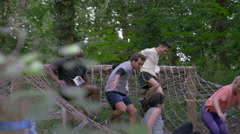 4K Competitors in endurance race climb over cargo net & pause to pose for photo Stock Footage