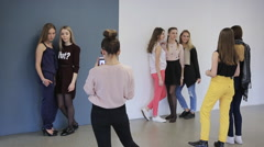Group of attractive girls trains in posing before going on photo session Stock Footage