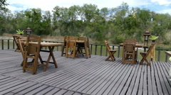 Wooden table and chair on terrace of the restaurant at waterside Stock Footage