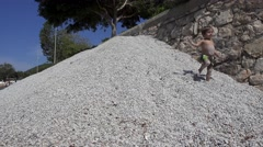 Child runs down from pebble heap Stock Footage