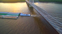 Aerial right to left pan of barge passing under bridge on Mississippi River Stock Footage